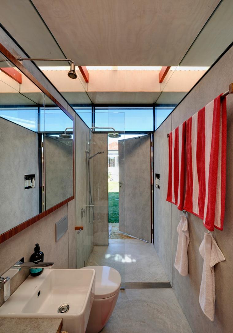 Bagno lungo e stretto, pavimento e pareti con piastrelle di colore chiaro