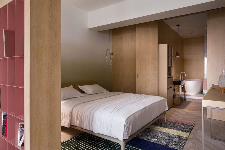 Camera da letto con bagno padronale a vista con vasca, pavimento in legno di colore chiaro