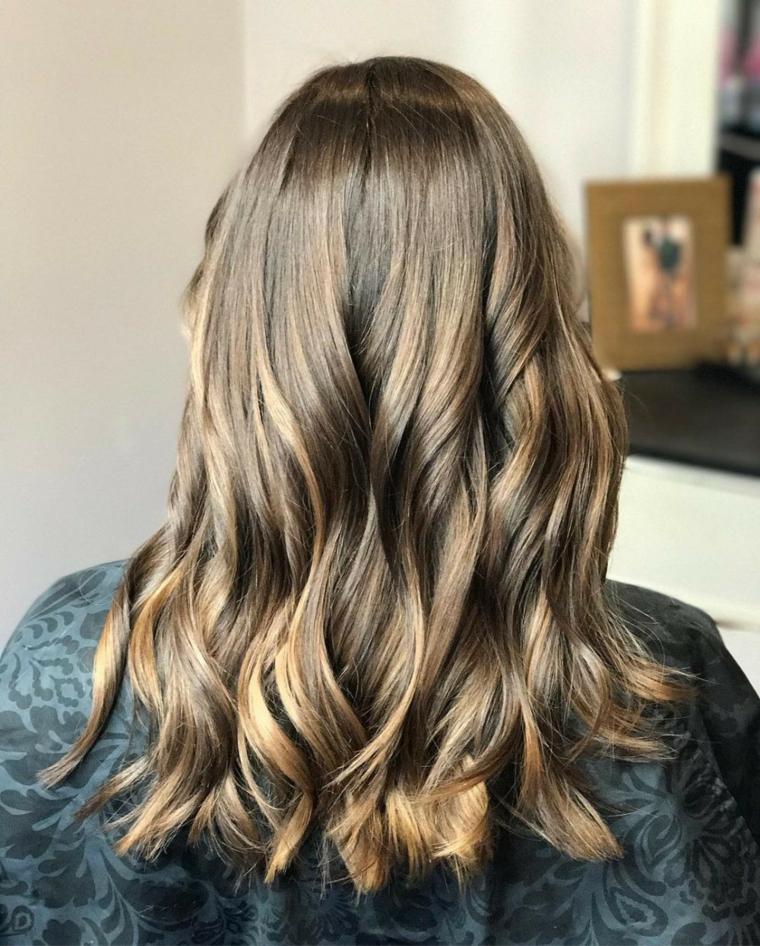 idea per un colore capelli nocciola con dei balayage caramello, piega leggermente ondulata