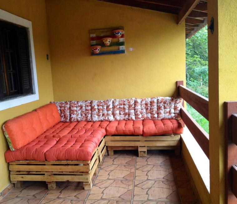 idea per arredare con divani in pallet per esterno completi di cuscini arancioni e bianchi a fantasia