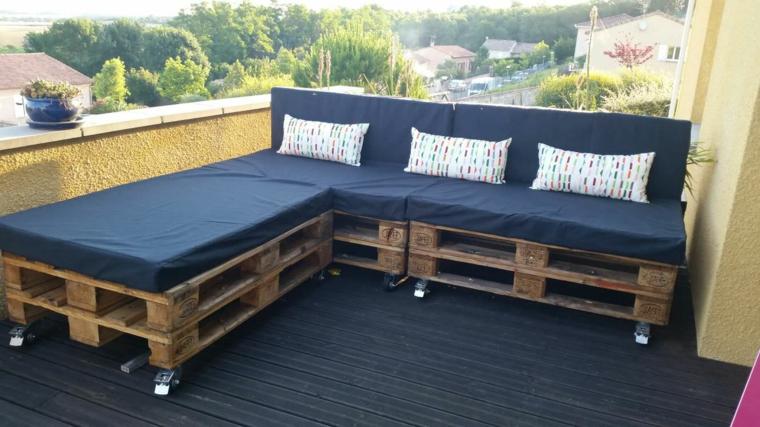 idea arredo giardino con bancali realizzato con un divano angolare con cuscini blu