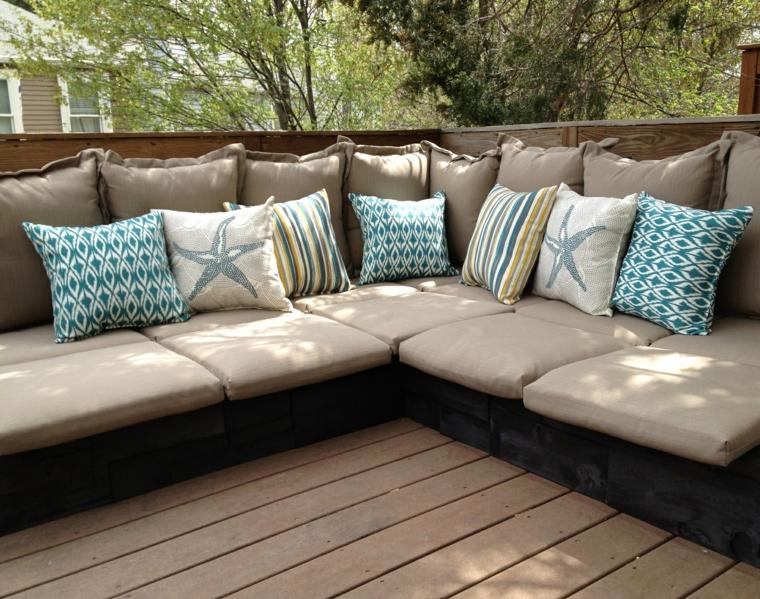 idea per un arredo giardino con bancali realizzato con un divano angolare e cuscini tortora e turchesi a fantasia