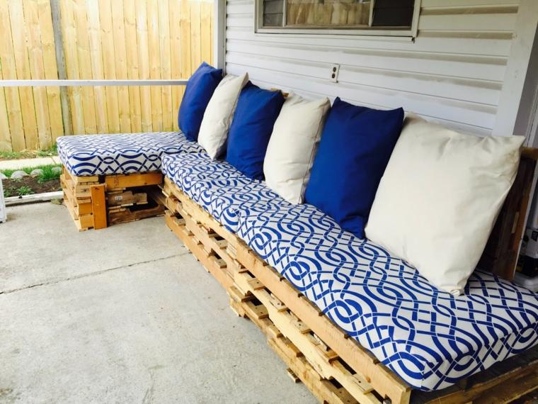 fai da te idea per un arredo giardino con bancali realizzato con un divano completo di cuscini bianchi e blu