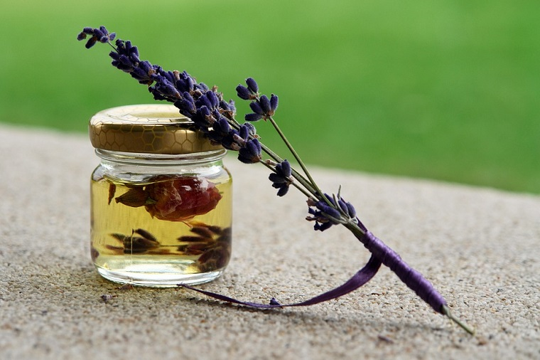 Oli essenziali bio, barattolino di vetro con olio all'interno, fiori di lavanda secchi
