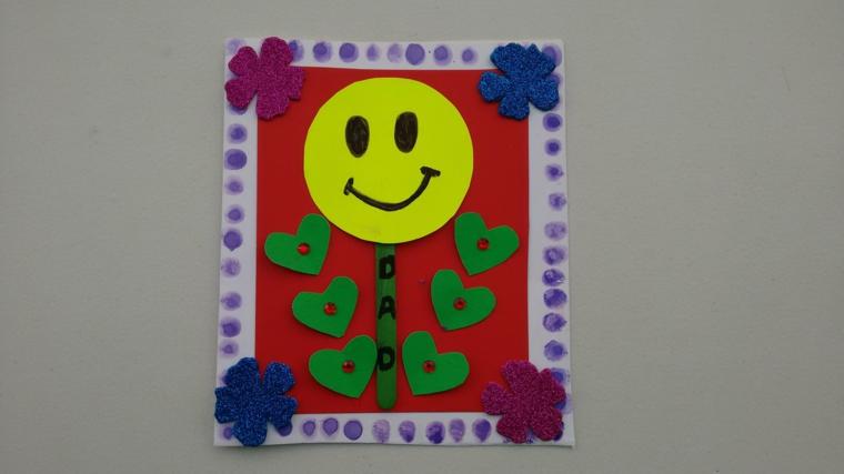 un cartoncini di auguri con dei cuori, fiori e uno smile: idea per lavoretti festa del papà