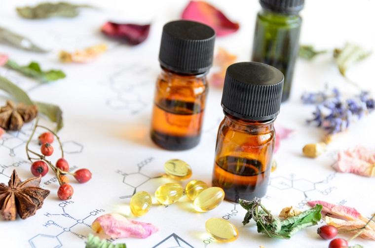 Idea metodo di cura con essenze vegetali, bottiglie di vetro con oli, ingredienti sul tavolo