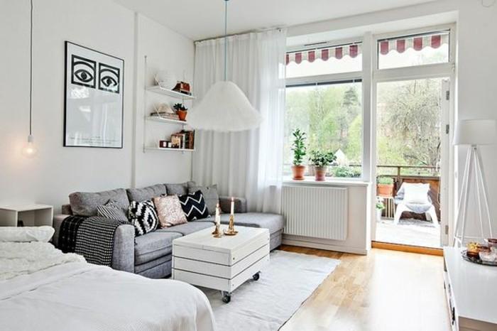 un'idea per arredare monolocale con balcone con un letto a due piazze e un divano grigio, pareti bianchi e pavimento in parquet
