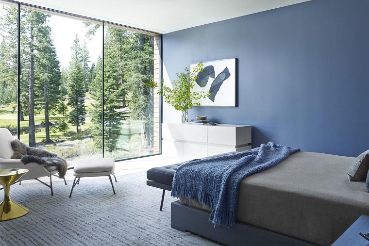 Zona notte con pareti di colore blu, stili di arredamento, pavimento con tappeto, grande finestra con bellissima vista