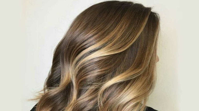 un'idea di capelli castano chiaro con delle sfumature dorate, piega morbida leggermente ondulata