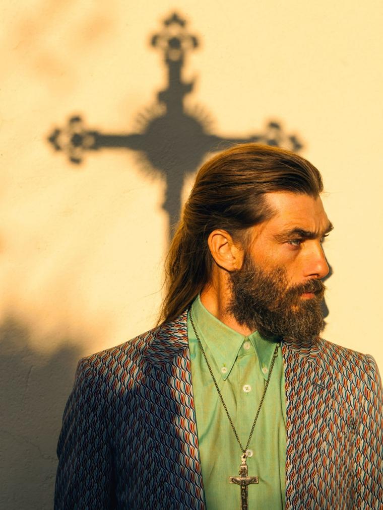 Idea tagli di capelli uomo lunghi, acconciatura legati indietro, accessorio ciondolo con croce