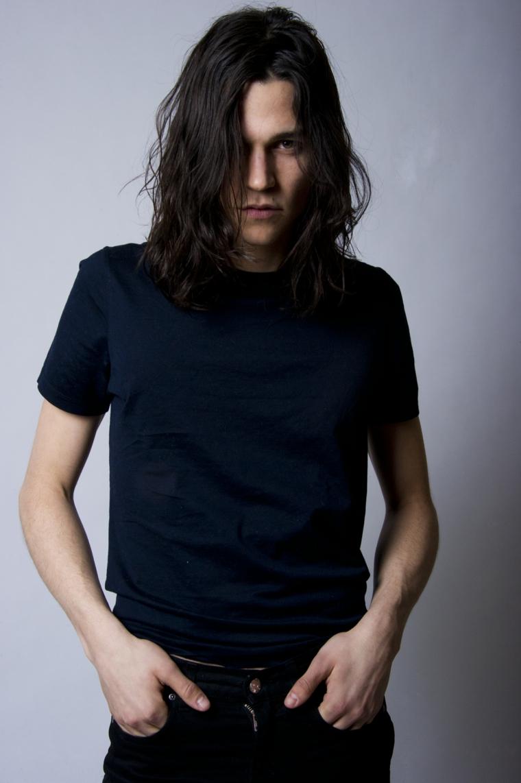 Acconciature uomo con capelli lunghi e mossi, colore nero, abbigliamento casual