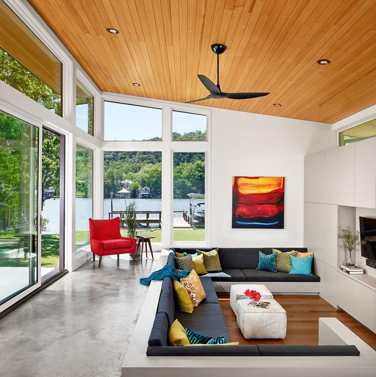 Idee per arredare casa, soggiorno con un divano a C, soffitto in legno con faretti, pavimento gres di colore grigio
