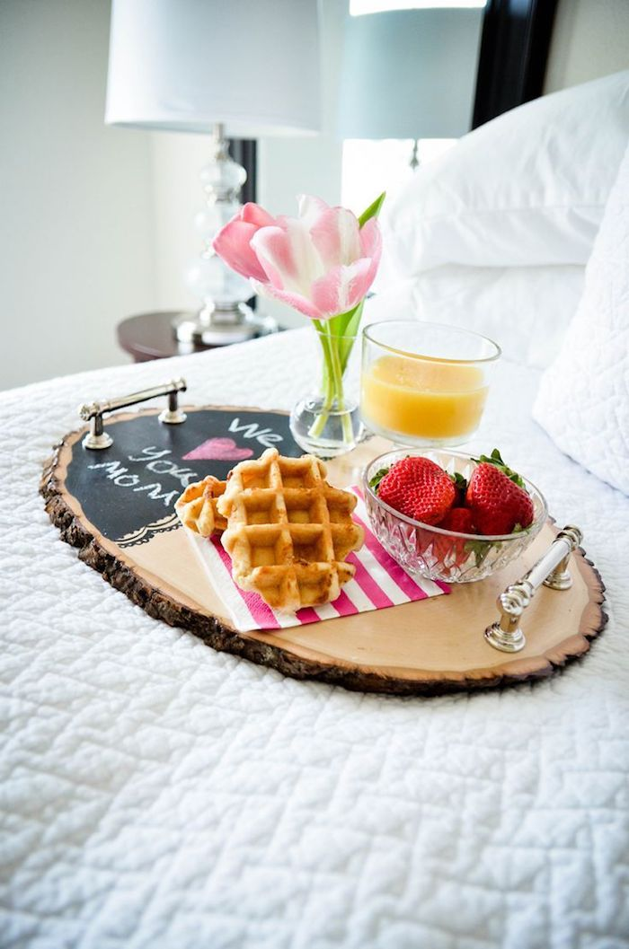 Fare la colazione a letto, ciotola con fragole, bicchiere con succo di frutta, vaso con fiori freschi