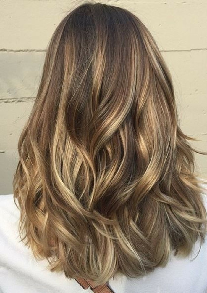 un taglio medio-lungo e dei balayage biondi su capelli castani leggermente ondulati