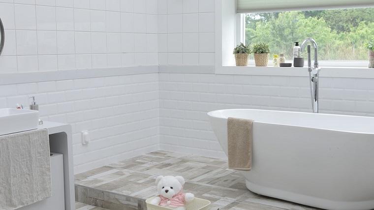 Arredo bagno moderno, tonalità di colore bianco, dislivello con vasca, finestra con tende a rullo