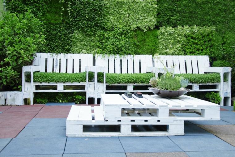 outdoor con un arredamento con bancali composto da un divano e da un tavoli dipinti di bianco