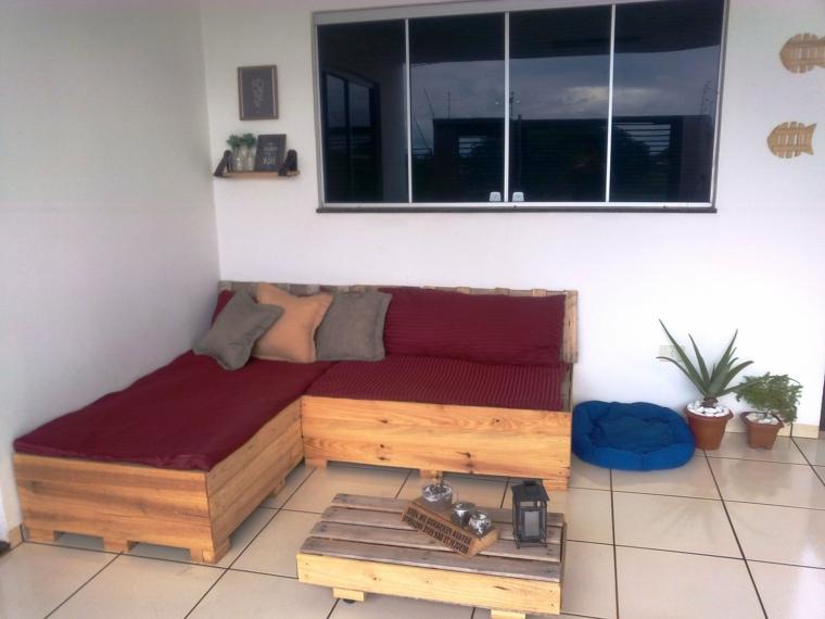 soggiorno arredato con dei divani con bancali completi di cuscineria bordeaux
