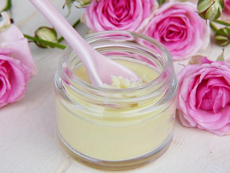 Metodo di cura basato su essenze vegetali, petali di rosa, barattolo di vetro con crema agli oli
