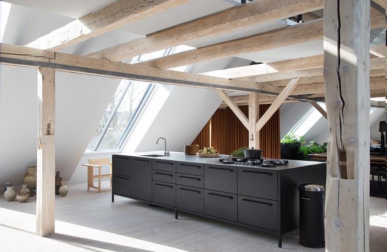 Case moderne interni, cucina in metallo di colore nero al centro della stanza, pavimento in legno colore chiaro, travi in vista