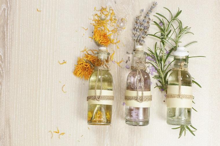 Oli essenziali in bottigliette di vetro, lavanda e rosmarino, tavolo di legno colore bianco