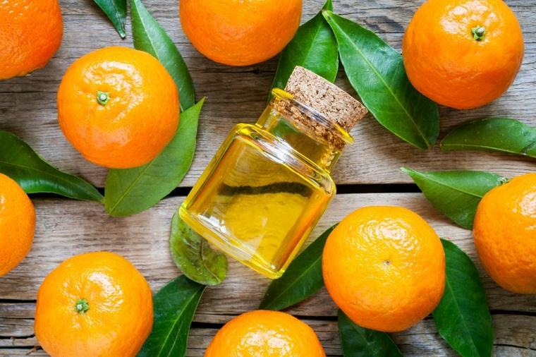 Bottiglietta di vetro con olio essenziale di agrumi, tanti mandarini con le foglie