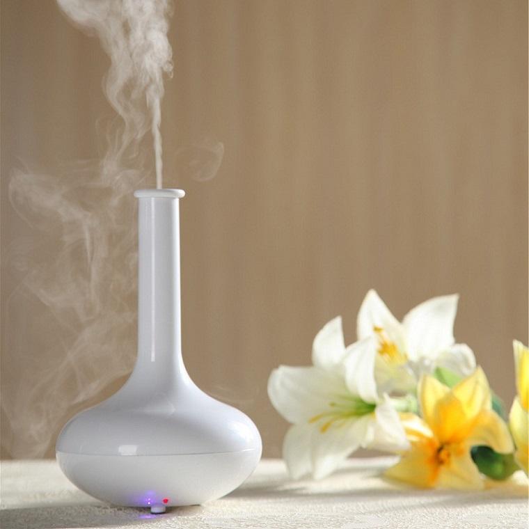 Oli essenziali per diffusori, elemento di design colore bianco, fiori bianchi sul tavolo