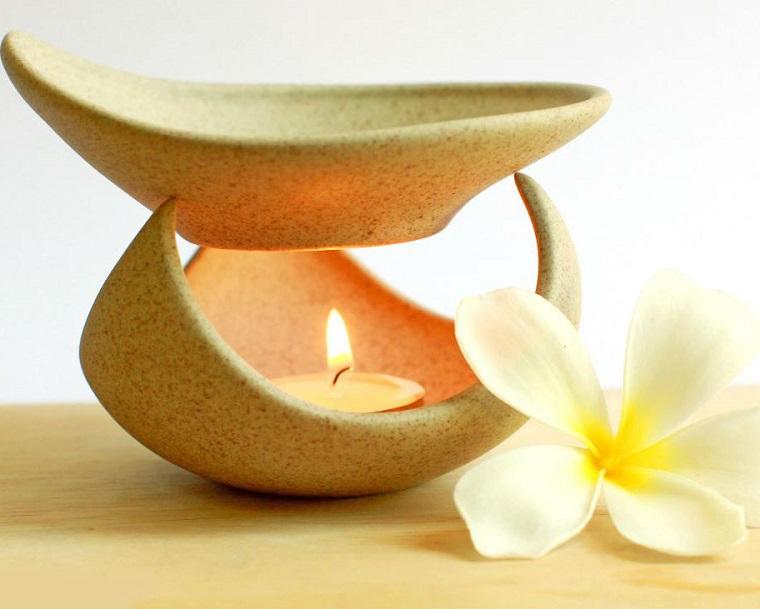 Aromaterapia con un diffusore di ceramica colore giallo, candela all'interno e fiore bianco