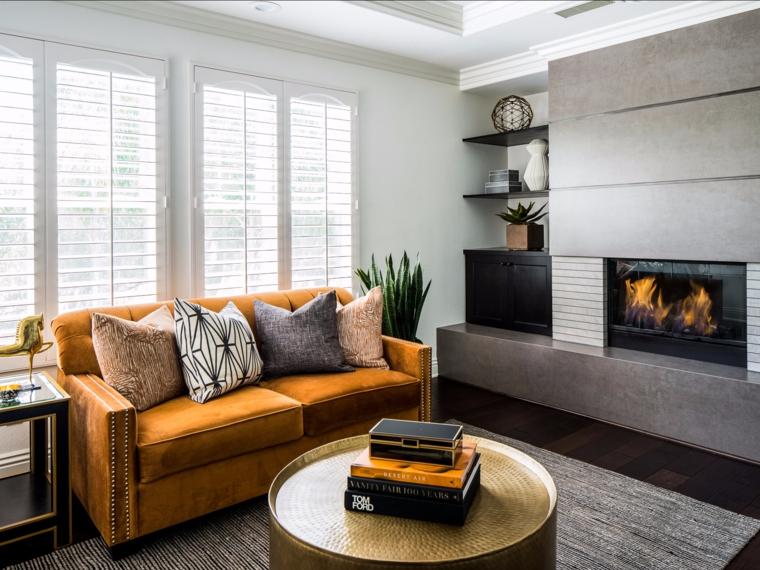 Soggiorno con un divano color senape, pavimento in legno scuro, stili di arredamento