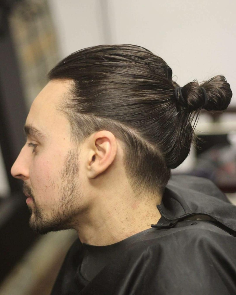 Capelli rasati uomo, raccolti con elastico, rasatura sotto, ragazzo giovane con barba