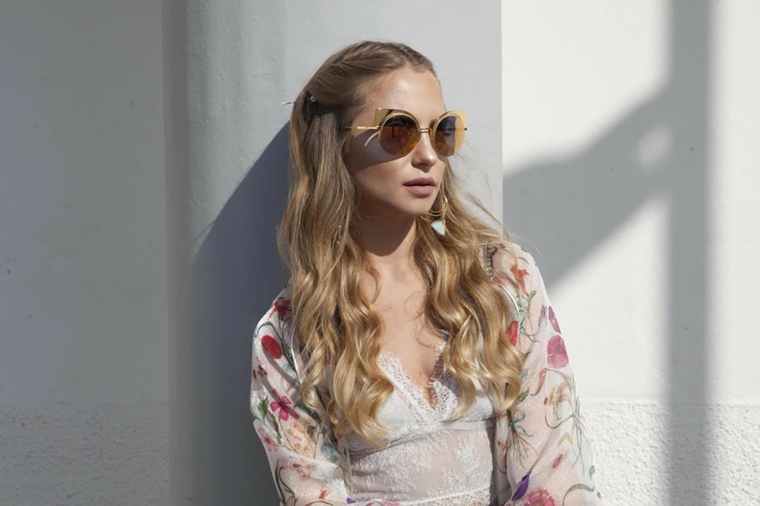 look alla moda con i capelli degradè e un semi raccolto con i boccoli, occhiali da sole e maglia bianca con fiori rossi