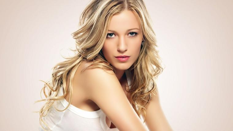 una ragazza con i capelli biondo cenere scuro, lunghi e con un'acconciatura ondulata