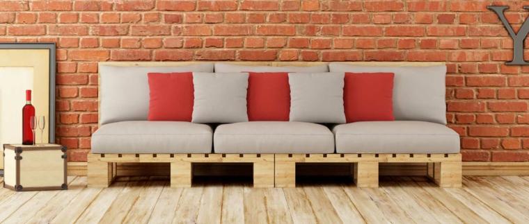 parete con mattoni a vista e dei divani con pedane completi di cuscini grigi e arancio