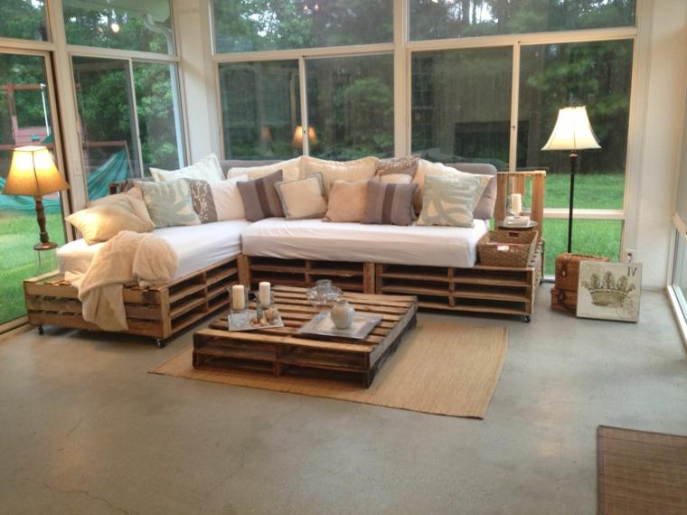 soggiorno con ampia vetrata arredato con panchine con bancali completi di cuscini e tavolino