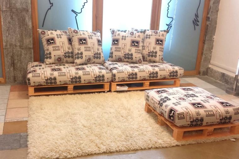 soggiorno arredato con un arredamento con bancali, un divano e un puff con cuscini bianchi con disegni scuri