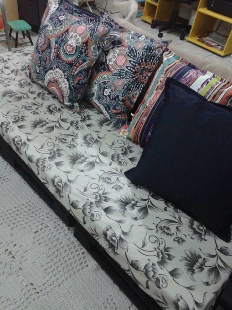 primo piano della seduta bianca con fiori nere e dei cuscini con delle fantasie colorate