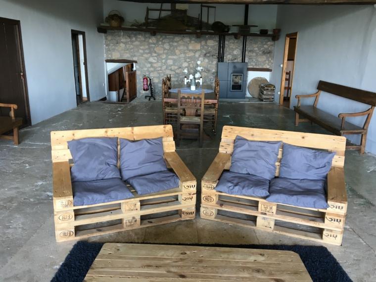 stanza parete rustica e due divani con pedane completi di cuscini azzurri