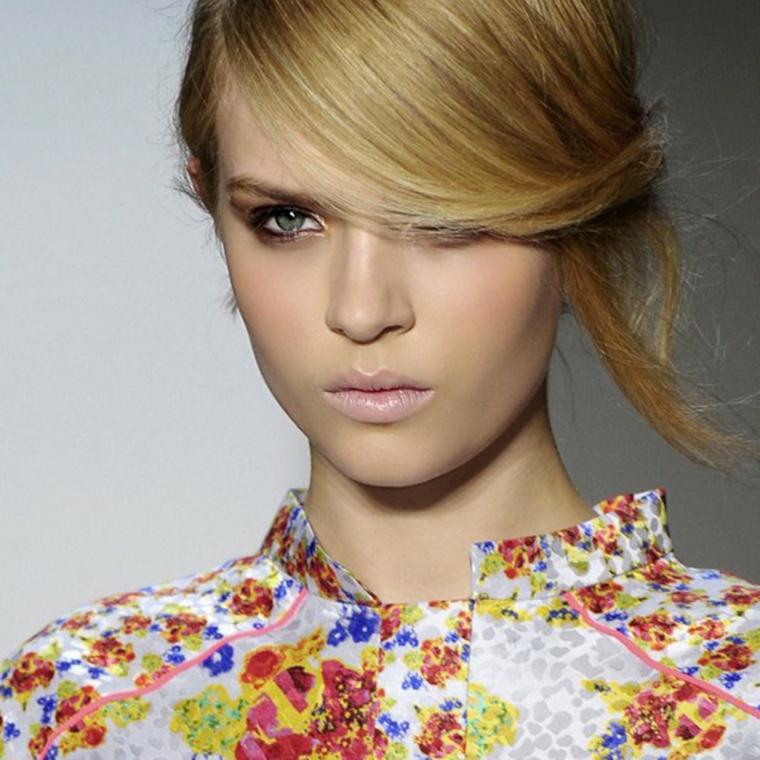 un'acconciatura raccolta che dà l'idea di un taglio corto, rossetto rosa e occhi azzurri