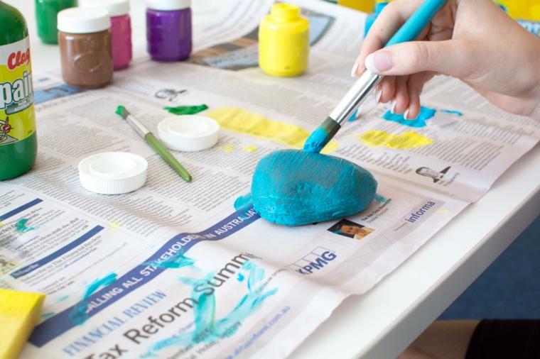 con un pennello e della tempera azzurra viene colorato un sasso: festa del papà lavoretti