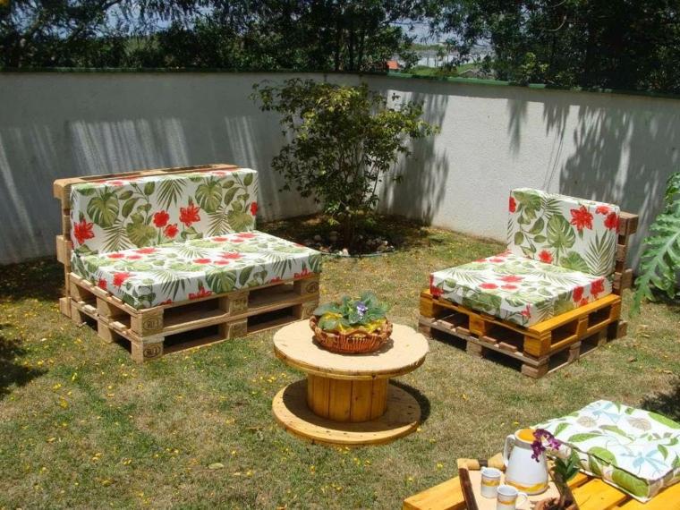 zona esterna arredata con dei pallet riciclati e trasformati in divani e tavolo rotondo