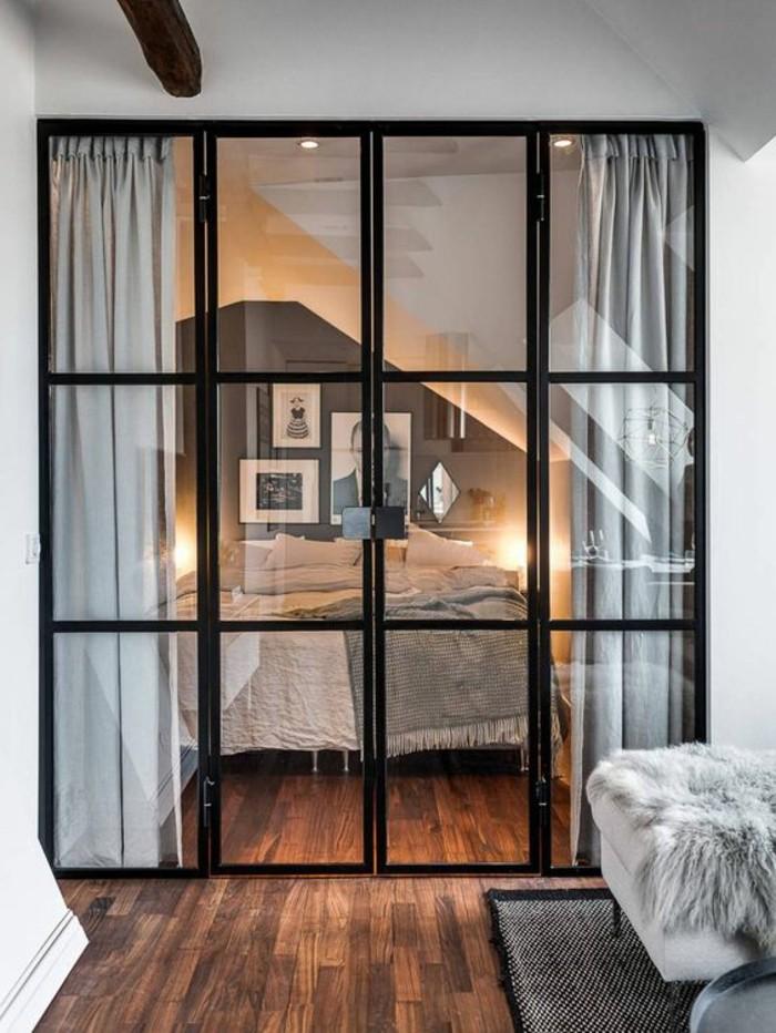 una vetrata con i profili neri funge da divisorio fra la zona giorno e quella notte: idee piccola casa