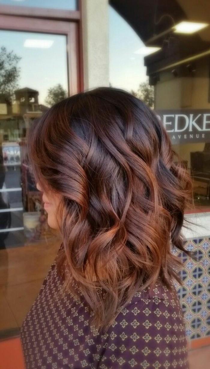 un'immagine di una ragazza dai capelli scuri con balayage, piega con morbide onde