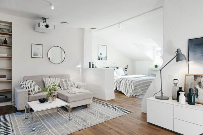 una proposta per arredare un monolocale con pareti e mobili bianchi, pavimento in parquet, specchio rotondo