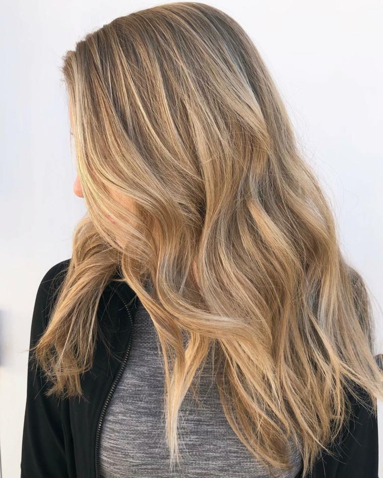 capelli lunghi con un balayage biondo su base castana chiara, piega morbida e ondulata