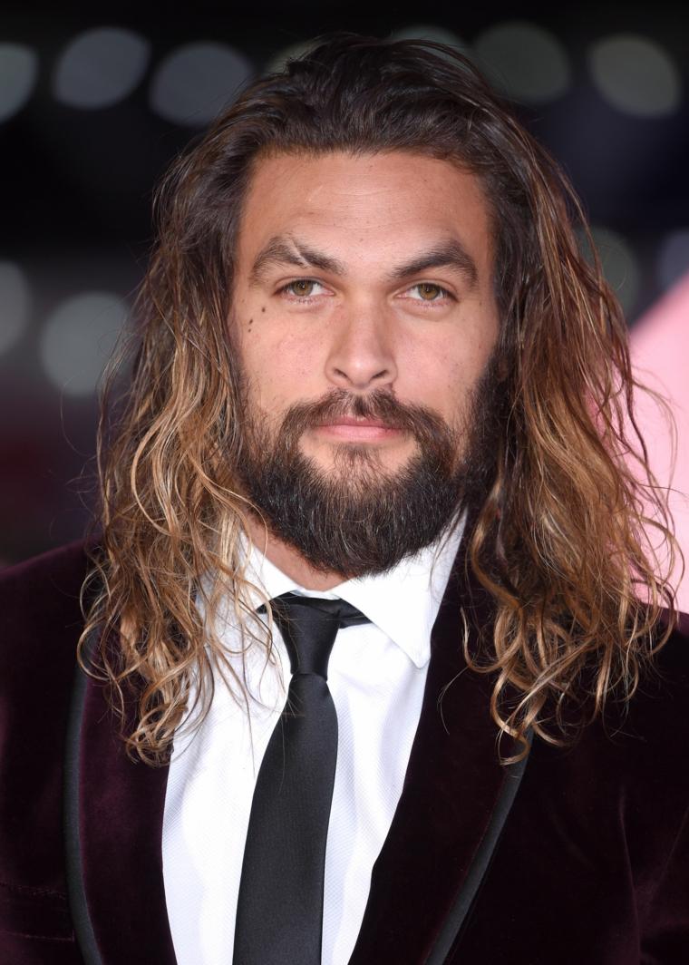 Uomini belli, l'attore Jason Momoa, acconciatura mossa capelli lunghi di colore chiaro