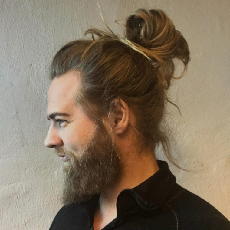 Uomini bellissimi, ragazzo sorridente con i capelli legati a chignon, colore biondo e barba