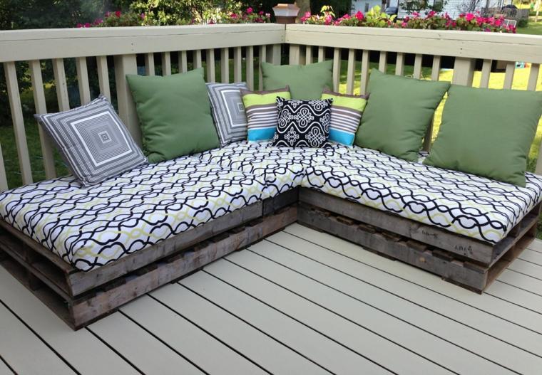 esterno con dei mobili con pallet, un divano angolare con cuscini verdi, grigie e bianchi e variopinti