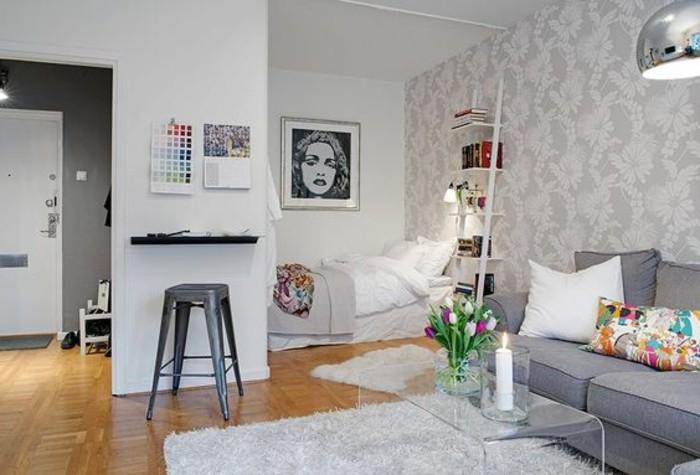 una proposta per come arredare monolocale con pavimento in parquet, divano grigio, sgabello grigio e tavolo-mensola