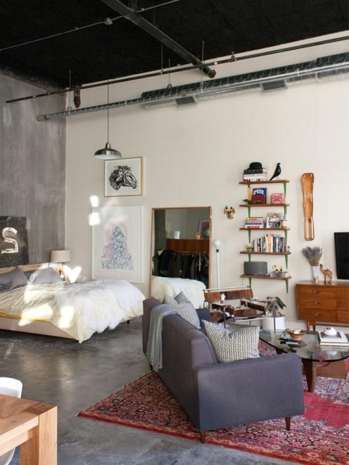 una proposta per arredare spazi piccoli con un divano grigio, mobile tv in legno, libreria essenziale e letto