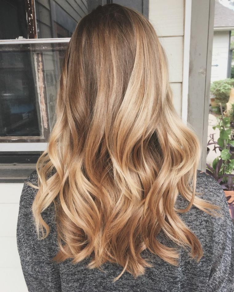 bellissimi capelli lunghi con un balayage biondo, piega ondulata sulle punte