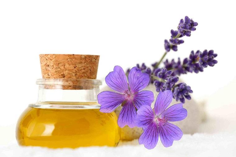 Cura con essenze vegetali, bottiglietta di vetro con olio di lavanda, fiori viola